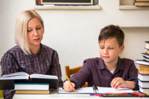 40159305 - young student learns at home with a his mom tutor.